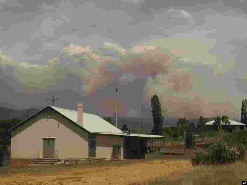 Asap dari kebakaran besar membubung dari perbukitan di belakang desa Numeralla, negara bagian New South Wales, Australia (8/1). (AP/Rod McGuirk)