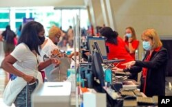 FILE - Travelers check in at Love Field airport, May 28, 2021, in Dallas.