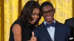 First lady Michelle Obama, pictured with Andre Massey of Deep Center Inc., Savannah, Ga., gives a sign of approval to the youth's father in the audience during the 2015 National Arts and Humanities Youth Program Awards at the White House, Nov. 17, 2015.