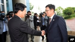 Suh Ho, head of South Korea's working-level delegation, right, shakes hands with his North Korean counterpart Park Chol Su upon his arrival for a meeting at Kaesong Industrial District Management Committee in Kaesong, North Korea.