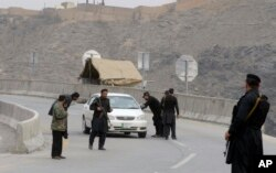 Pakistani police officers stand guard while their colleagues searching a car at a checkpoint on the highway leading to Torkhum, a border crossing between Pakistan and Afghanistan, March, 20, 2017.