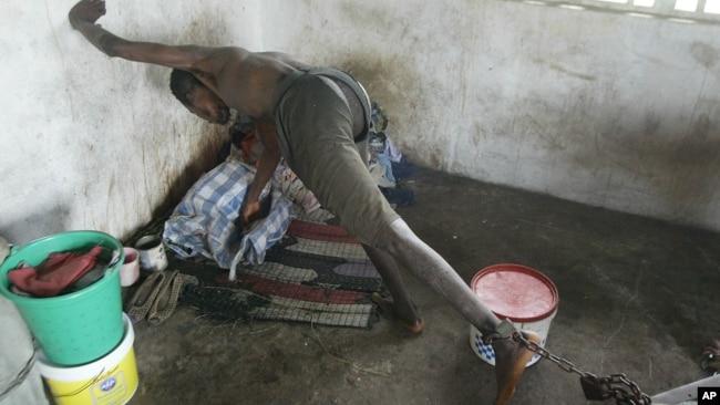 资料照片:利比里亚蒙罗维亚圣灵精神病院一名被拴着脚铐的患者。(2003年8月29日)
