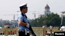 یک مامور پلیس اسلحه بدست در میدان تیانانمن پکن - ۴ ژوئن ۲۰۱۴
