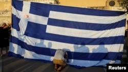 Arhiva - Demonstrant kleči ispred grčke zastave odajući počast, tokom protesta protiv mera štednje, 29. juna 2015.