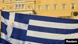 A protester kneels to pay his respect in front of a Greek flag during an anti-austerity rally in Athens, Greece, June 29, 2015. Stunned Greeks faced shuttered banks, long supermarkets lines and overwhelming uncertainty on Monday as a breakdown in talks be