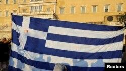 Des manifestants s'agenouent devant le drapeau grec à Athènes, Grèce, le 29 juin 2015.