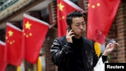 FILE: A smoker puffs while passing a restaurant in Beijing, May 11, 2015. China is enforcing strict new rules on tobacco advertising as of Sept. 1.