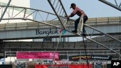 Seorang pekerja konstruksi membongkar tenda di panggung utama yang digunakan untuk aksi protes di jalan utama Bangkok, Thailand.