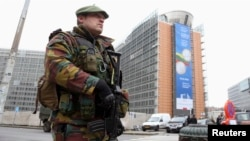 FILE - A Belgian soldier, one of hundreds deployed to guard potential terror targets, stands outside the European Commission headquarters in Brussels, Jan. 21, 2015.