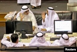 FILE - Investors watch a monitor at the Dubai Financial Market.