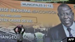 """Seorang perempuan berdiri dekat poster kampanye seorang caleg Cisse Ibrahima """"Bacongo,"""" di ibukota Abidjan, Pantai Gading (19/4)."""