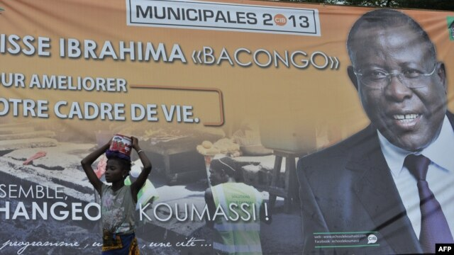 "A girl stands next to a campaign poster of Cisse Ibrahima ""Bacongo,"" a candidate for the municipal elections, on April 19, 2013 in Abidjan, two days ahead of the vote."