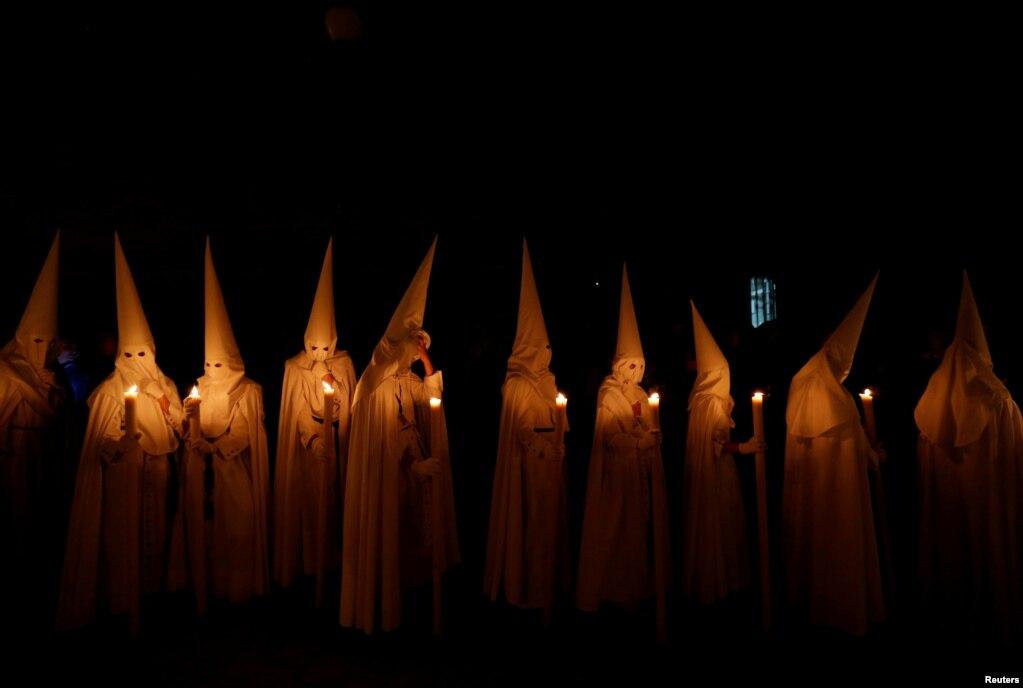 Кающиеся братства Ла-Паса (Мир) принимают участие в крестном ходе Во время Страстной недели в андалузской столице Севилье, Испания, 14 апреля 2019 года.