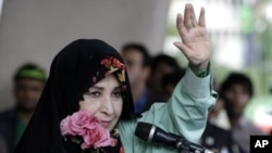 In this Tuesday, June 9, 2009 file photo, Zahra Rahnavard, the wife of reformist candidate Mir Hossein Mousavi, waves to the people during a rally at Heidarnia stadium, during the final days of the election race in Tehran, Iran.