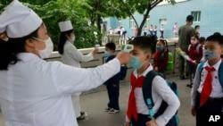 지난해 7월 북한 평양 김성주소학교에서 교직원이 등교하는 학생의 체온을 재고 있다.