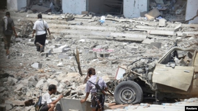 Soldiers are pictured through a window as they inspect the scene of a car bomb attack at a military police building in Mukalla city of the southern Yemeni province of Hadhramout. May 11, 2014.