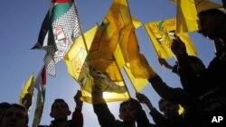 지난달 31일 파타 창설 48주년 기념식에서 팔레스타인 기와 파타 기를 흔드는 주민들.
