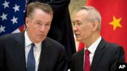FILE - Chinese Vice Premier Liu He, right, talks with U.S. Trade Representative Robert Lighthizer, while they line up for a group photo in Beijing, Feb. 15, 2019..