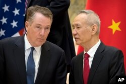 Chinese Vice Premier Liu He, right, talks with U.S. Trade Representative Robert Lighthizer, while they line up for a group photo in Beijing, Feb. 15, 2019.