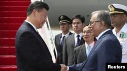시진핑 중국 국가주석(왼쪽)이 14일 방글라데시 데카 공항에 도착한 후 환영 나온 압둘 하미드 방글라데시 대통령과 악수하고 있다.