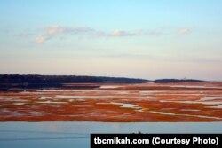 Boatmen glide past a vibrant marsh on a bay near Salt Pond Visitor Center at the Cape Cod National Seashore in Massachusetts.