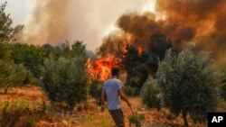 A man walks toward wildfires in Kacarlar village near the Mediterranean coastal town of Manavgat, Antalya, Turkey, July 31, 2021. The death toll from wildfires raging in Turkey's Mediterranean towns rose to six Saturday.