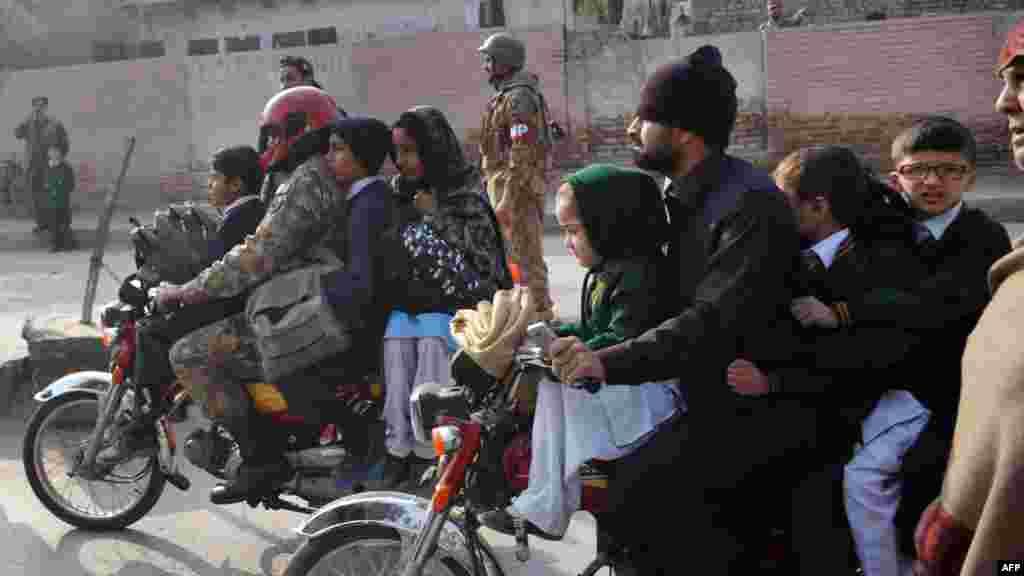 والدين پاکستانی با فرزندانشان محل حادثه حمله مردان مسلح به مدرسه ای در پيشاور را ترک می کنند-- ۲۵ آذر (۱۶ دسامبر)