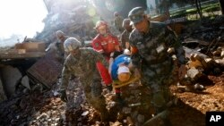 In a disaster drill, soldiers from Chinese PLA Southern Theater Command Army and the U.S. Army Pacific carry an injured man from a mock earthquake-collapsed building as they conducting a joint rescue operation in the U.S.-China Disaster Management Exchange drill at a training base in Kunming, China, Nov. 18, 2016.