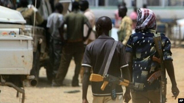 Armed men walk past on April 17, 2011 as resentment towards the capital Khartoum runs high in the restive town of Abyei, on the Sudanese north-south border, which suffers from chronic underdevelopment despite its strategic importance and the area's rich n