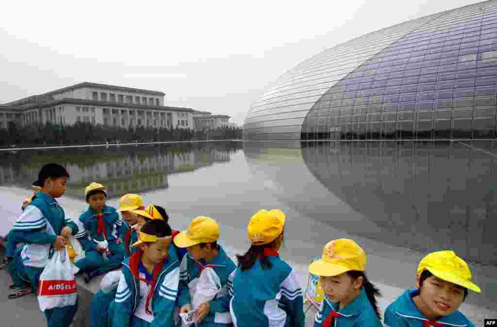 """学童聚集在北京中国国家大剧院外(2007年9月29日)。2018国家大剧院国际戏剧季/著名导演作品邀请展,邀请了德国柏林邵宾纳剧院演出话剧《人民公敌》。该剧通常在演出中安排观众与演员对话,让观众表明是否支持剧中主角将水源污染的真相公诸于世的立场。在北京9月上旬的首演中,一些观众在互动环节中表示:""""希望有言论自由"""",""""中国媒体也不讲真话"""",""""我们政府一样不负责任""""。这引发当局不安。国家大剧院方面强令剧团删掉互动部分。尽管余下的两场演出删除了对话环节,但仍有观众喊出""""为了个人的权利,为了自由""""。"""