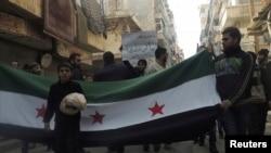 叙利亚1月10日的反政府示威,男孩在反政府组织旗帜前手捧面包