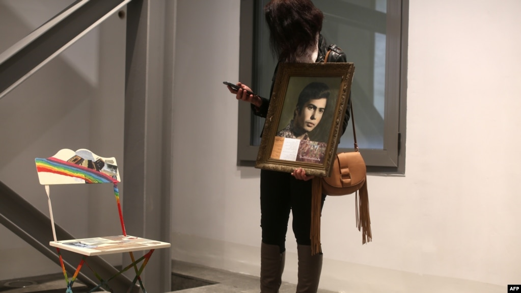 Nibal holds a portrait of her brother Ghaleb, a Lebanese man who went missing during the Lebanese civil war, as she stands next to an empty chair during an exhibit in Beirut, April 13, 2017.