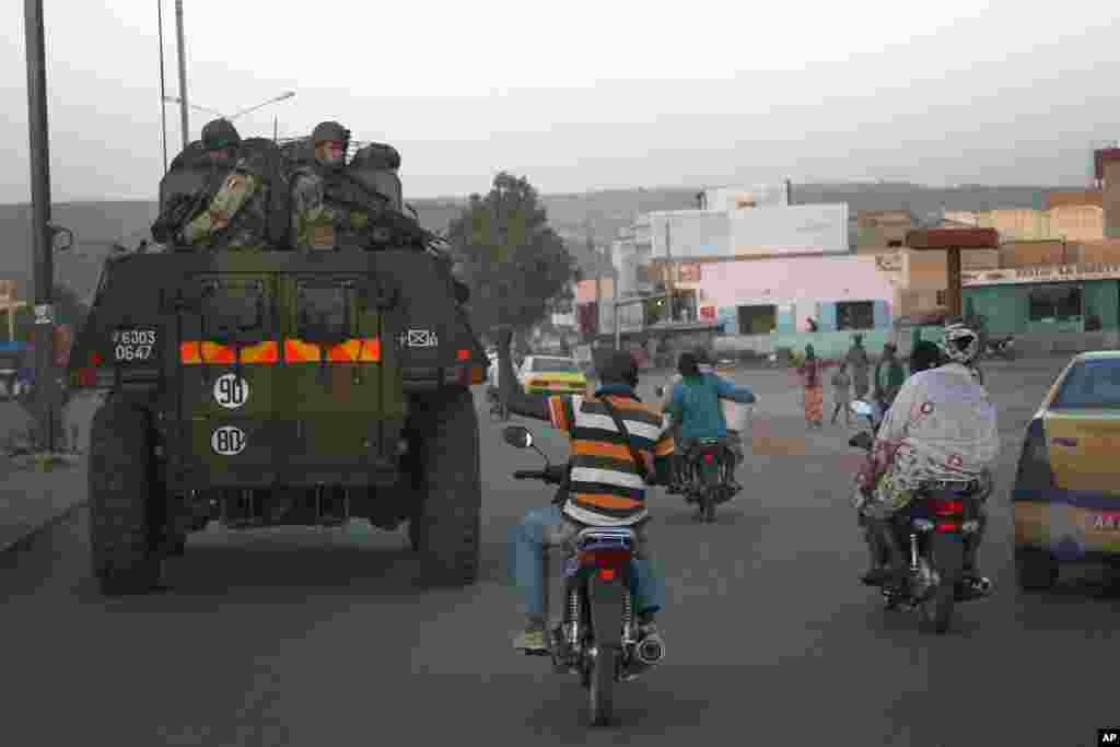 A motorcyclist waves his support as French troops in two armored personnel carriers drive through Mali's capital Bamako on the road to Mopti, January 15, 2013.