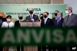 The Director of Brazil's National Health Surveillance Agency Antonio Barra speaks at a press conference regarding the CoronaVac vaccine, flanked by Sao Paulo Gov. Joao Doria, right center, in Brasilia, Brazil, Wednesday, Oct. 21, 2020. (AP Photo)