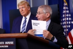 FILE - President Trump listens as Director of the National Institute of Allergy and Infectious Diseases Dr. Anthony Fauci speaks during a coronavirus task force briefing at the White House, April 5, 2020, in Washington.