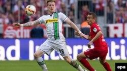 L'attaquant Rafinha de Munich, à droite, et André Hahn de Gladbach se battent pour récupérer un ballon lors du match de football de la Bundesliga entre le Bayern Munich et le Borussia Moenchengladbach au stade Allian, à Munich, Allemagne, 30 avril 2016.