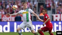 L'attaquant Rafinha de Munich, à droite, et André Hahn de Gladbach se battent pour récupérer un ballon lors du match de la Bundesliga entre le Bayern Munich et le Borussia Moenchengladbach au stade Allian, à Munich, Allemagne, 30 avril 2016.