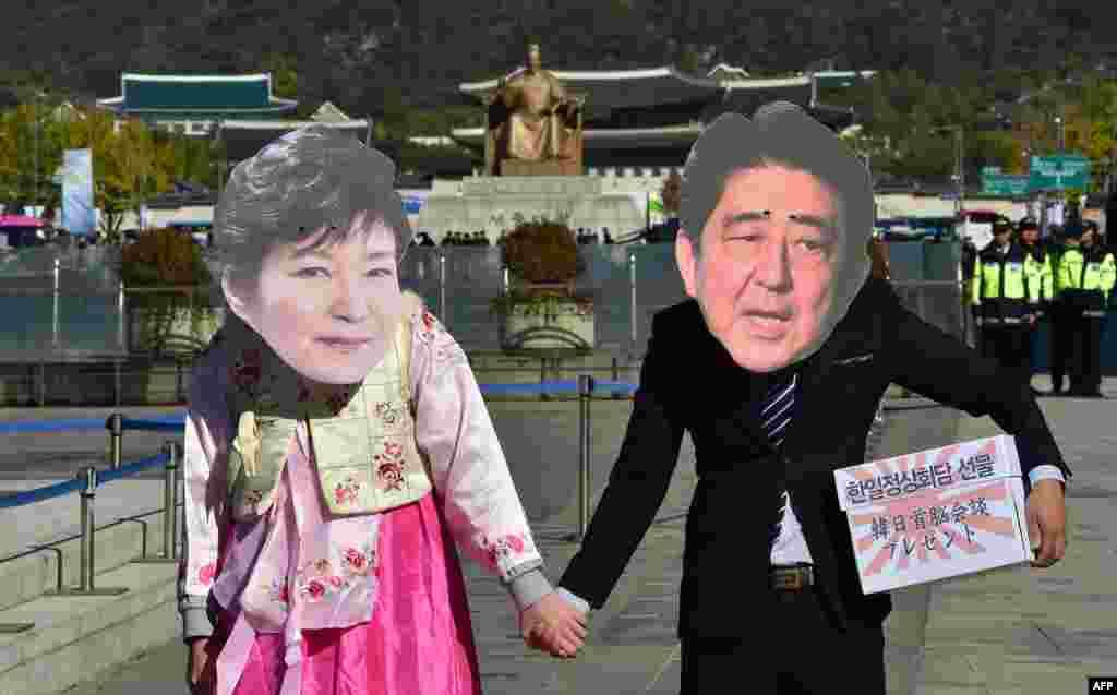Những người biểu tình đeo mặt nạ hình Tổng thống Hàn Quốc Park Geun-Hye (trái) và Thủ tướng Nhật Bản Shinzo Abe nắm tay nhau trong một cuộc biểu tình chống Nhật Bản ở Seoul. Những người biểu tình phản đối chuyến đi sắp tới của ông Abe tới Seoul tham dự một cuộc hội kiến cấp cao với bà Park.