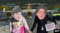 FILE - Protesters wearing masks depicting South Korean President Park Geun-Hye (L) and Japanese Prime Minister Shinzo Abe (R) hold hands during an anti-Japanese rally in Seoul. South Korea President Park Geun-hye and Japanese Prime Minister Shinzo Abe promised to resolve the long-standing dispute over comfort women by year's end.