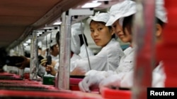 In this 2010 file photo, workers assemble electronics in a Hon Hai, also known as Foxconn, factory in southern Guangdong province May 26, 2010. The factory is a main supplier for Apple's products.