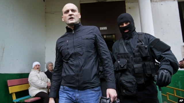 A police officer escorts Russian opposition leader Sergei Udaltsov, center, for questioning in Moscow, October 17, 2012.
