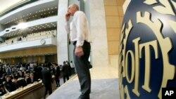 Un membre du personnel de l'OIT debout à côté d'un panneau montrant le logo de l'OIT, avant l'ouverture de la 95e Assemblée de l'Organisation internationale du travail (OIT) au siège européen des Nations Unies à Genève , Suisse, mercredi 30 mai 2007. (KEYSTONE / Salvatore Di Nolf