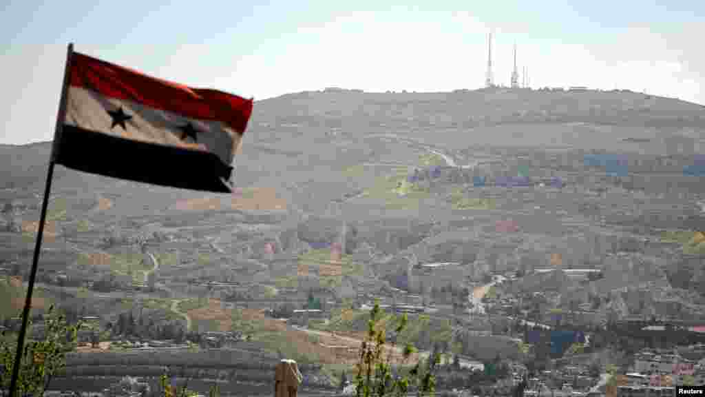 A Syrian national flag flutters as Qasioun mountain is seen in the background from Damascus, Syria, April 7, 2017.