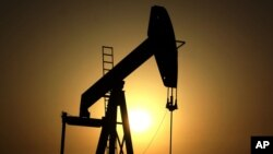 FILE - The sun sets behind an oil pump in the desert oil fields of Sakhir, Bahrain, June 8, 2011. OPEC nations have agreed in theory on the need to reduce their production to help boost global oil prices during a meeting last month in Algeria, but disagre