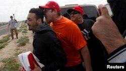 川普總統的支持者在南加州一個海灘對著反對川普總統的示威者叫喊。
