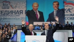 Russian President Dmitry Medvedev, right, and Prime Minister Vladimir Putin wave during a United Russia party congress in Moscow, September 24, 2011.