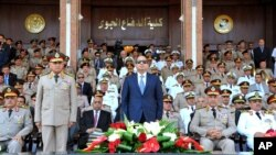 FILE - In this July 22, 2015, photo provided by the office of the Egyptian Presidency, Egyptian President Abdel-Fattah el-Sissi, (C), and Defense Minister Sedqi Sobh, (L), stand at attention at the Air Defense Academy in Alexandria, Egypt. Maj-Gen. Mohammed Ali el-Sheikh, an Egyptian army general who retired about 18 months ago, has been named the country's supply minister.