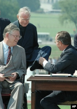 The Rev. Harold H. Wilke, top left, accepts a pen from President George Bush with his left foot, after Bush signed into law the Americans with Disabilities Act of 1990 at a White House South Lawn ceremony July 26, 1990.