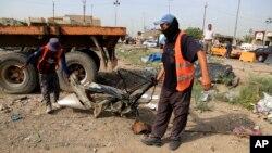 이라크 바그다드에서 12일 발생한 차량 폭탄 테러 현장에서 인부들이 잔해를 청소하고 있다.