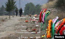 FILE - Men walk along graves of soldiers and civilians who were killed during a military conflict over the breakaway region of Nagorno-Karabakh, in Stepanakert, Nov. 2, 2020.